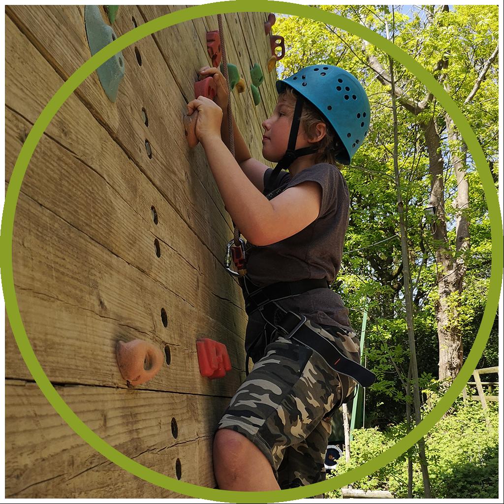 young boy in blue helmet climbing a rock wall