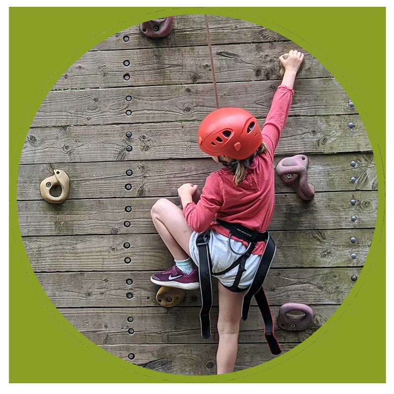 young girl climbing rock wall