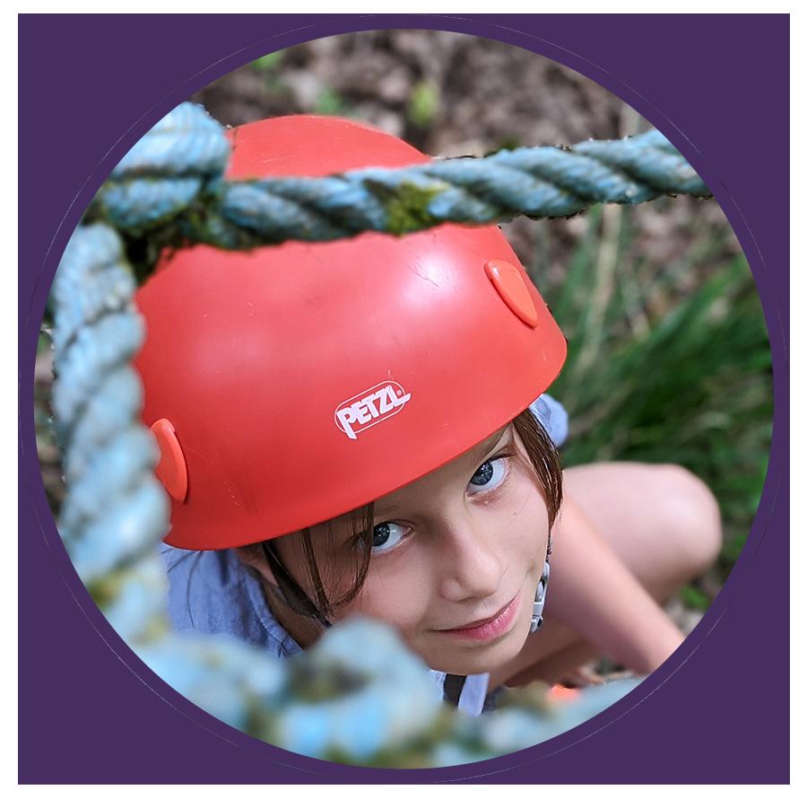 girl wearing red helmet on rope climb