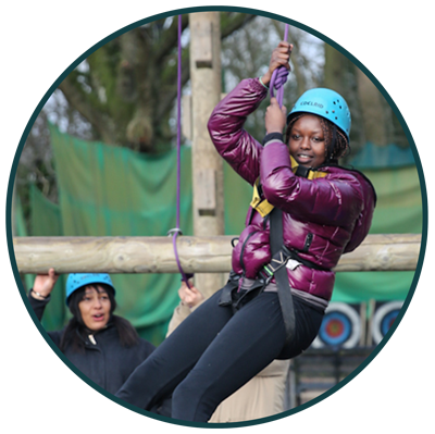 young girl in blue helmet on a rope