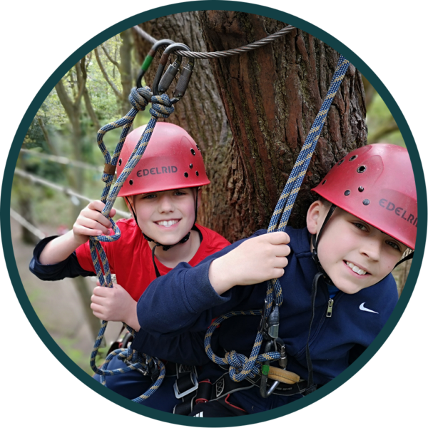 circle cropped image of two children on high ropes