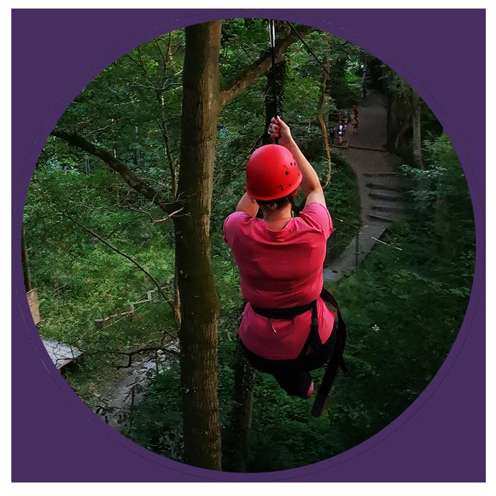 woman in red helmet on a zipline