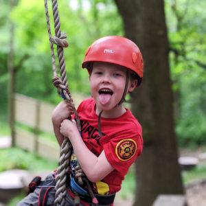 boy in red helmet sticking his tongue out on a rope