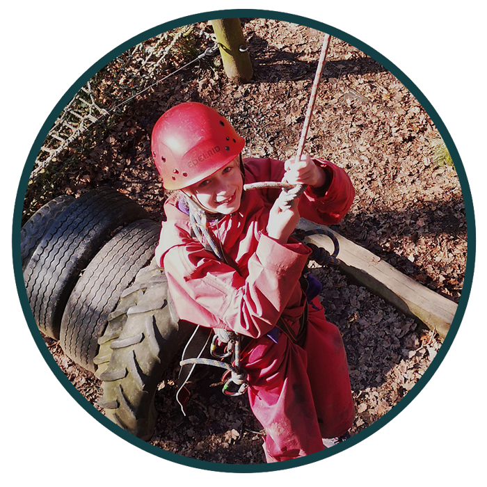 young girl in red swinging from a rope